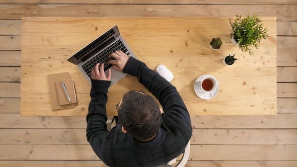 Thumbnail for Young bearded man drinking coffee or tea while working on laptop