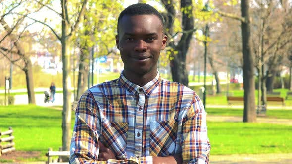 Thumbnail for A Young Black Man Folds His Arms Across His Chest and Smiles at the Camera in a Park on a Sunny Day