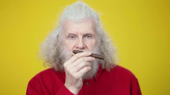 Thumbnail for Headshot of Stylish Senior Man Smelling Cigar Looking at Camera