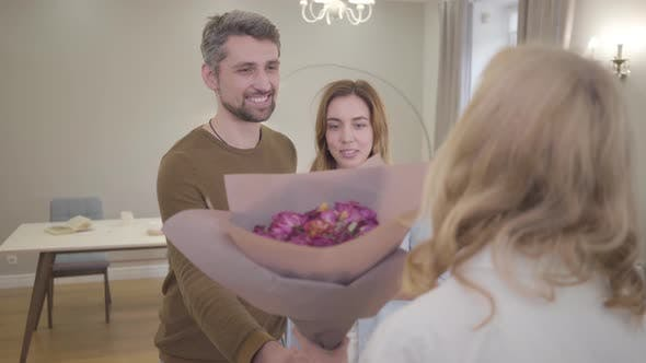 Thumbnail for Portrait of a Young Caucasian Couple Giving Bouquet of Violet Roses To the Woman with Blond Hair