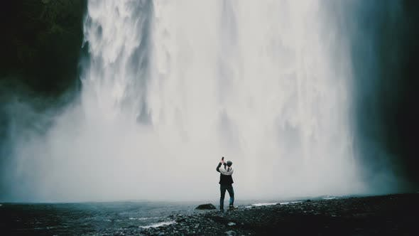 Thumbnail for Back View of Young Handsome Man Standing Near Powerful Gljufrabui Waterfall in Iceland and Taking