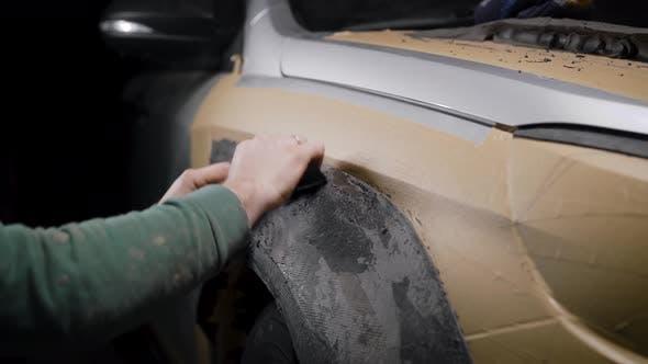 Master Is Making Plasticine Model for Tuning Car Body in Garage Polishing Billet in Dark Studio