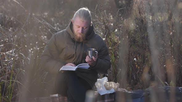 Thumbnail for Nachdenklicher kaukasischer Mann sitzt auf Baumstamm, liest und trinkt heißen Tee aus Stahl. Einsam
