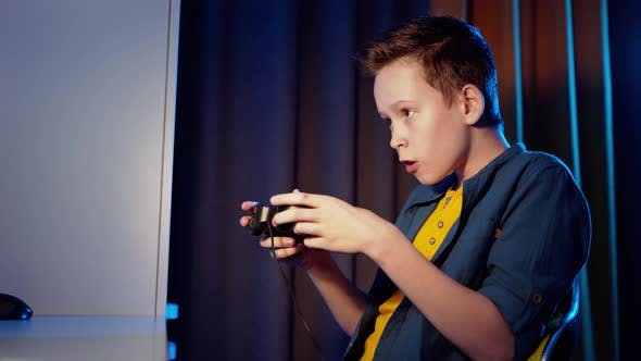 Thumbnail for Side view of a boy playing games at home
