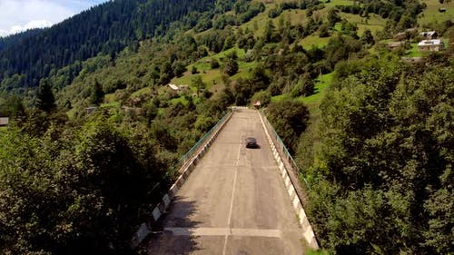Car Driving on Alpine Road on Mountains Background