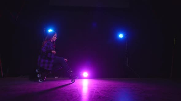 Thumbnail for Approaching View of Pink Light of Spotlight Between Blue Lamps and a Roller-skating Girl Sitting on