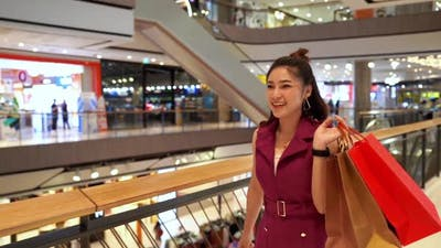 slow-motion of young woman walking with shopping bags in the mall