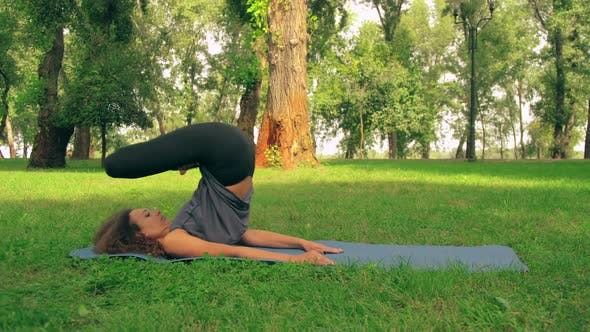 Thumbnail for Young Slim Female Doing Yoga Outdoor
