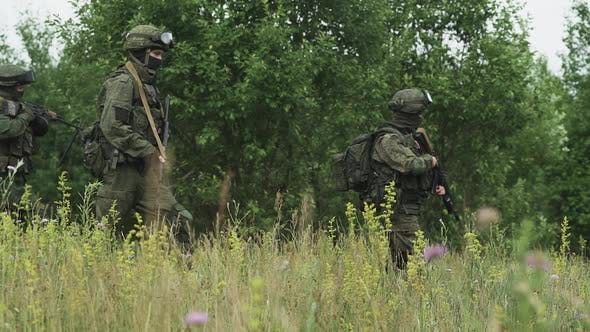 Soldiers in Camouflage with Assault Rifle Walking Through the Field Military Action in the Steppe
