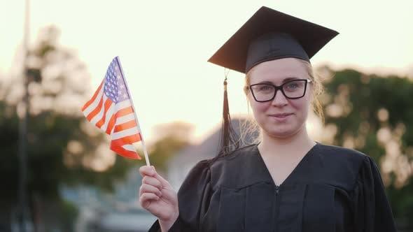 Thumbnail for Rückansicht eines Absolventen mit der Flagge von USA in der Hand. Studieren in Kanada