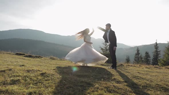 Thumbnail for Newlyweds. Caucasian Groom with Bride Dancing on Mountain Slope. Wedding Couple