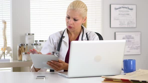 Thumbnail for Female doctor working on touchscreen and laptop computer