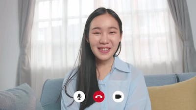 Asian Woman Talking To Camera In Home Living Room