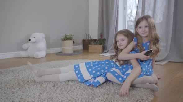 Thumbnail for Two Cute Caucasian Girls Sitting on Soft Carpet Indoors with Remote Control, Twin Sisters in Blue