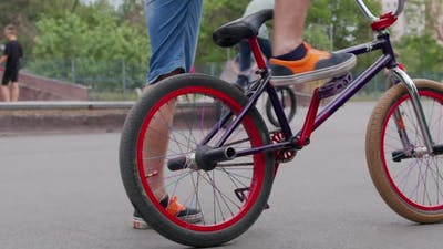 SLOW MOTION: Unrecognizable Extreme Bmx Biker Riding Bike in Sunny Park in Beautiful Summer.