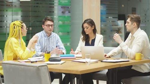 Jeunes gens élégants partageant avec le savoir, l'information lors de la réunion