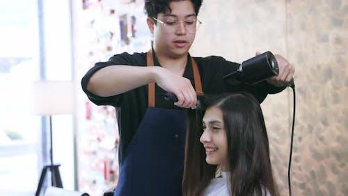 Hairdresser Using Hairdryer on Customer