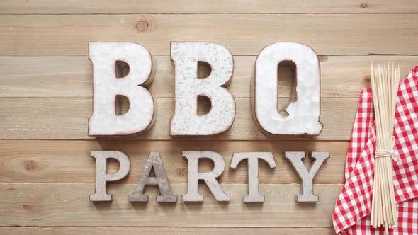 Metal BBQ Party sign with grilling tools on wood background.