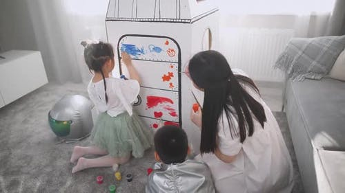 An Asian Female with Kids Play in the Living Room at Home a Boy in an Astronaut Costume Sitting on