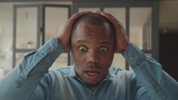 Shocked African Man with Hands on Head