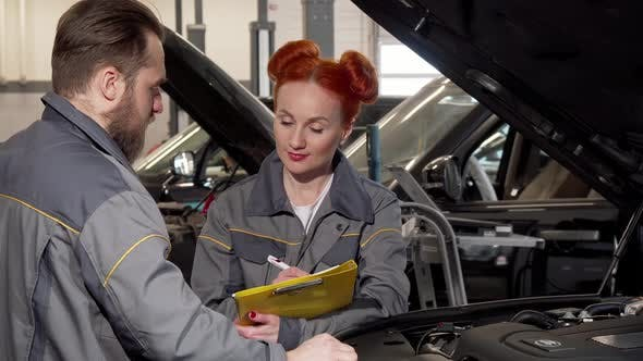 Thumbnail for Beautiful Female Mechanic and Her Male Colleague Examining Engine of a Car