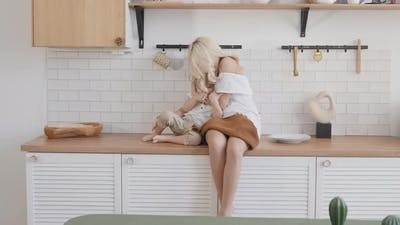 Blonde Woman with Her Son in the Kitchen