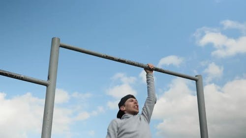 Pull ups with one hand. Man makes pull-ups on turnstile