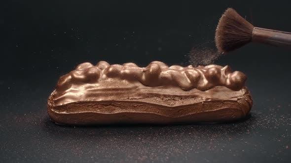 Thumbnail for Eclair in Chocolate Glaze with Almond Is Sprinkled with Gold Powder, Confectioner at Work