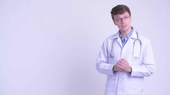 Thumbnail for Happy Young Handsome Man Doctor Presenting Something