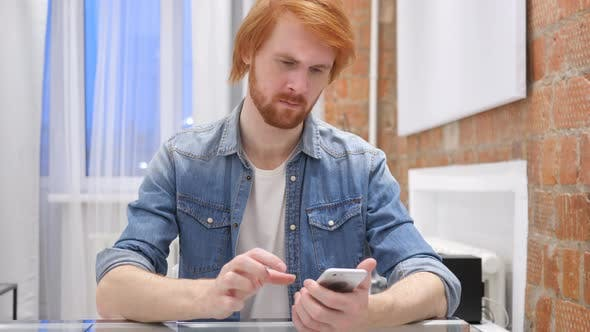 Thumbnail for Redhead Beard Man Using Smartphone for Online Browsing