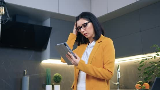 Woman in Glasses and Stylish Orange Jacket Standing in Cozy Kitchen and Using Tablet Device