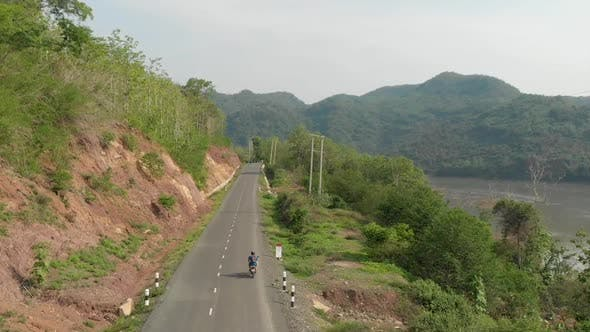 Aerial view of Motorcyclist on road next to Mekong River, Laos