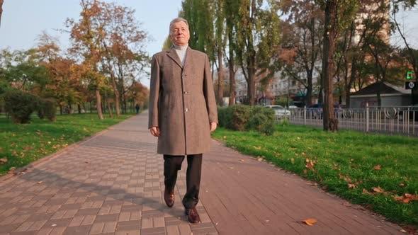 Mature Stroll in Park in Fall