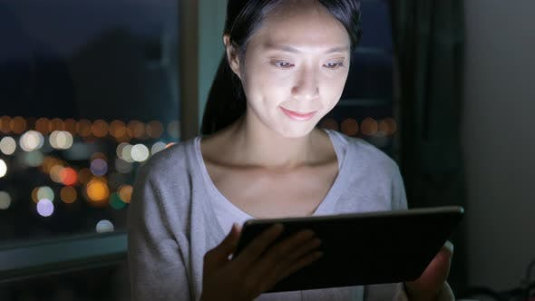 Thumbnail for Woman browsing on digital tablet at home