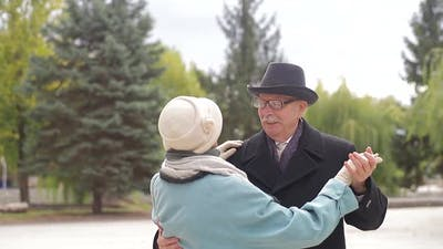 Old European man and woman dancing together in park standing.