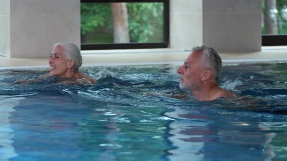 Thumbnail for Joyful Aging Couple Swimming in Hotel Pool Indoors