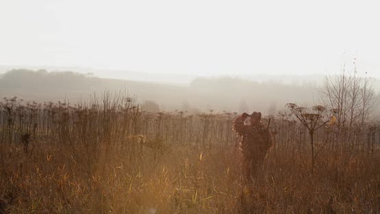 Thumbnail for Hunter in Hunting Equipment with Rifle on His Shoulder Walks Through the Field in Sun Light