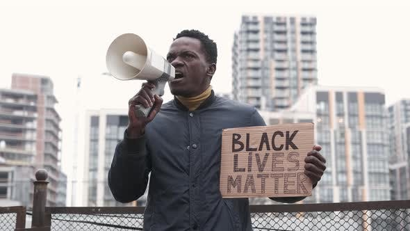 African American Man Holds Megaphone and Shouts