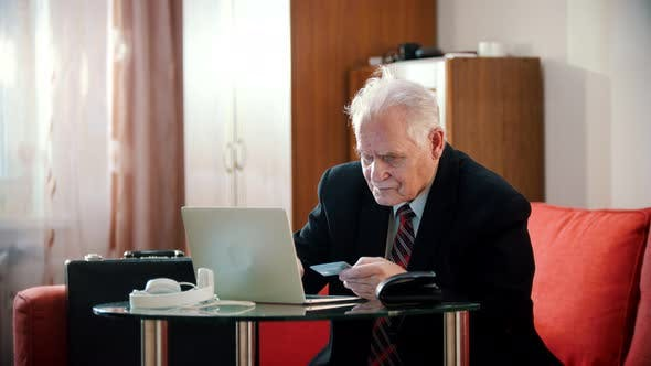Thumbnail for Elderly Grandfather - Old Grandfather Is Entering Bank Card Number Into Laptop