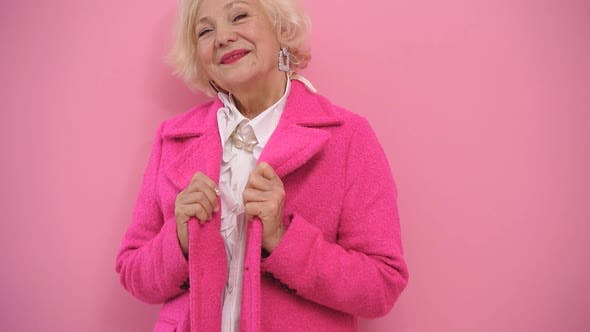 Stylish Mature Lady in a Modern Coat Poses for the Camera Without Thinking About Her Age, Isolated