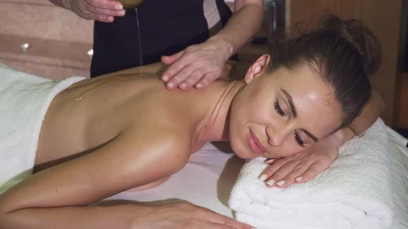 Thumbnail for A Professional Masseuse Pours a Customer with Oil and Massage Her