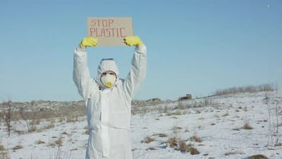 Man Wore in Protective Suit Raise Stop Plastic Sign on Abandoned Place in Winter