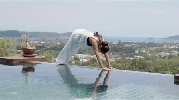 Relaxed Woman Doing Baby Cobra Exercise Near Swimming Pool Against Beautiful Scenery