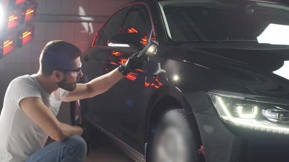 Thumbnail for Man überprüft Ergebnis des Polierens des Autos mit einer Taschenlampe.