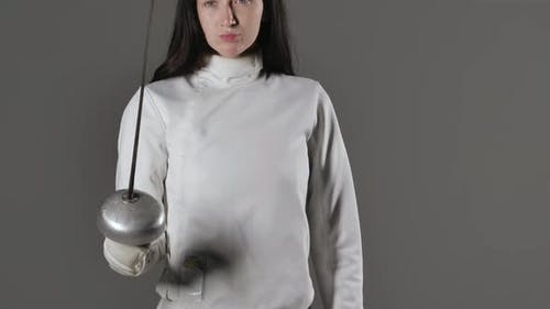 Portrait of a Young Woman Fencer in a White Uniform Posing with a Rapier in Her Hands on a Gray