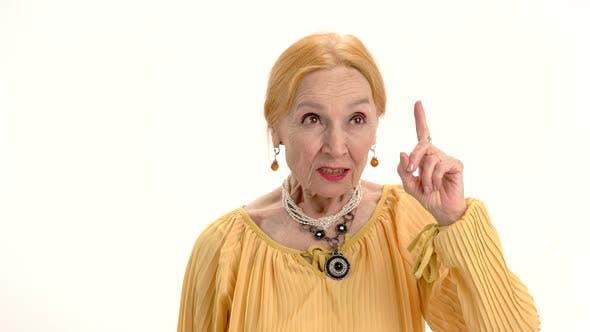 Elderly Woman with Raised Finger