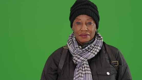 An older black woman in warm clothes on green screen