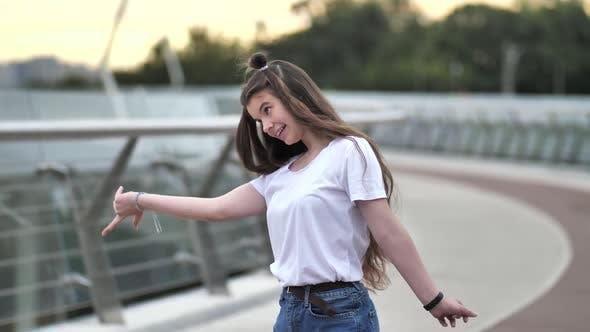 Pretty Teen Girl Cheerfully Dancing on Footbridge
