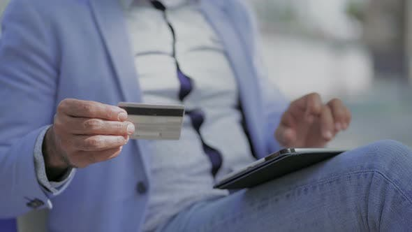 Thumbnail for Cropped Shot of Man with Credit Card Using Tablet Pc