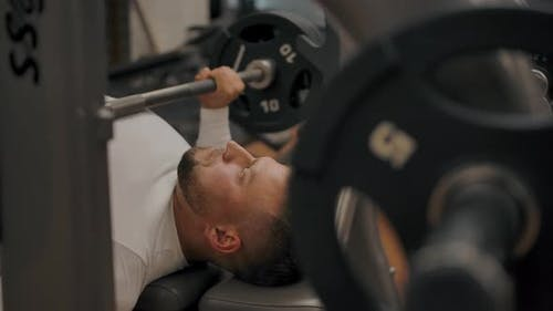 Powerful Man Does a Bench Press with a Barbell